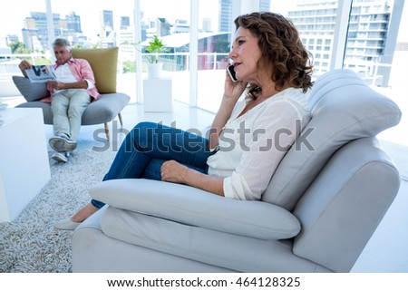 Woman talking on phone while man reading newspaper at home #464128325