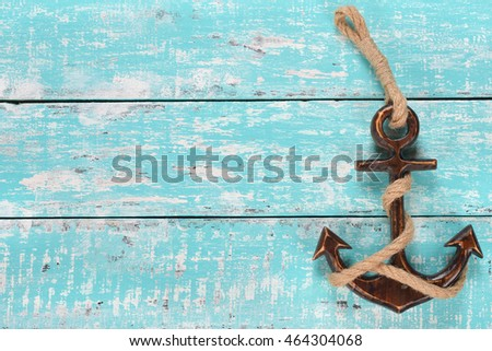Wooden decorative anchor on the vintage background