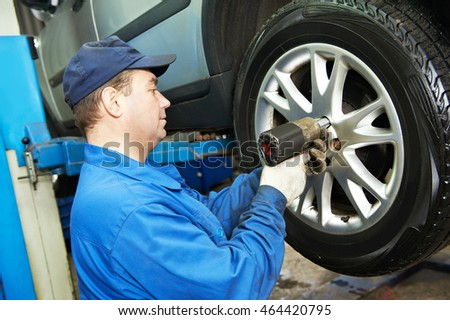auto mechanic screwing car wheel by wrench #464420795
