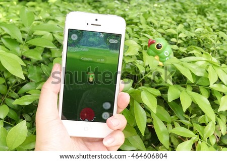 BANGKOK - AUG 6, 2016 : Apple iPhone5 held in one hand showing its screen with Pokemon Go application, catching Caterpie, bug-typed Pokemon. This app is worldwide hit after its launch. #464606804