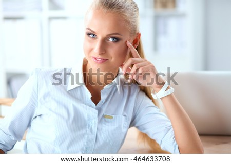 Attractive businesswoman sitting on a desk with laptop in the office #464633708