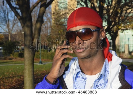 closeup of a young African American man on a cell phone call in an outdoor setting #46483888