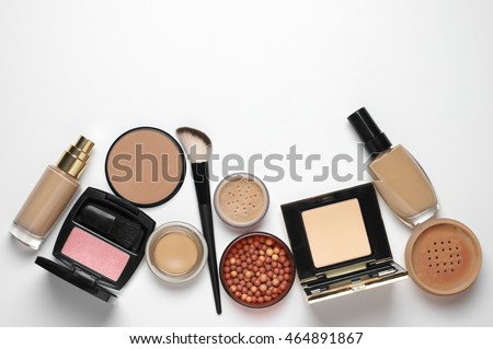 Make-up cosmetics set of liquid and cream foundations, compact and loose powder in various tones, bronzing pearls, blush and brush on white background. Top view point. #464891867
