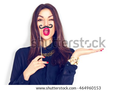 Surprised winking model Girl holding funny mustache on stick and showing empty copy space on open hand palm for text, white background. Girl presenting point. Proposing product. Advertisement gesture #464960153