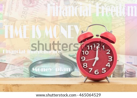 Red old fashioned alarm clock on Calculator with coin and Magnifying glass on money banknotes Euro and Dollars,with Written word Time is money #465064529