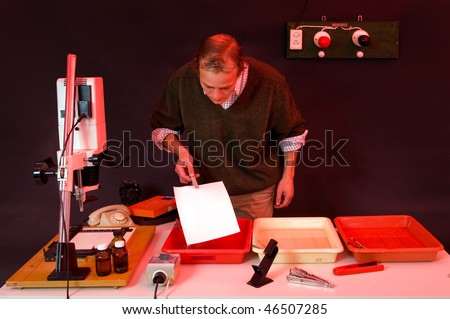 Photographer printing photos in a dark room, putting the freshly exposed sheet in the develop bath