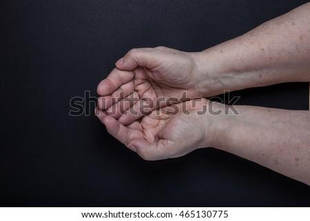 Hands of elderly woman on black background. #465130775