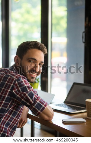 Portrait of happy handsome man working on laptop computer in restaurant or cafe. Cheerful man smiling for camera. #465200045
