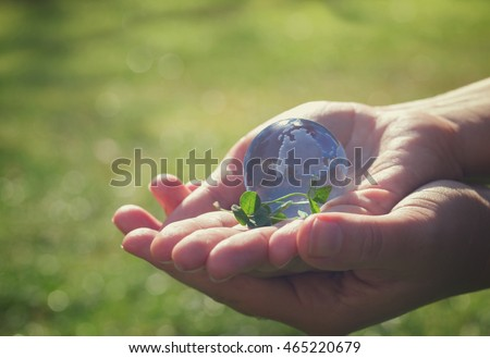 Two hands holding glass globe outdoor, concept for environment protection, retro toned #465220679