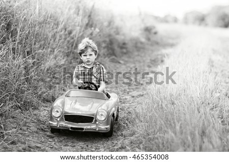 Little preschool kid boy driving big toy car and having fun with playing, outdoors. Child enjoying warm summer day in nature landscape. Old picture in black and white.