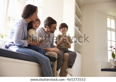 Family Sitting On Window Seat At Home Together #465373553
