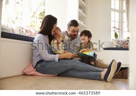 Family Sitting On Floor Reading Story At Home Together #465373589