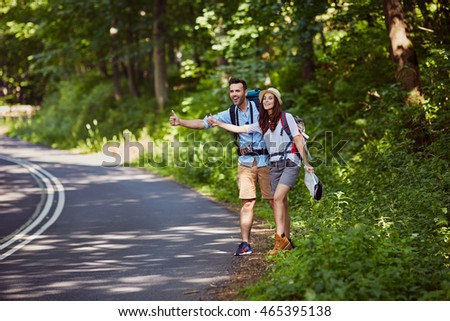Attractive couple hitchhiking in mountains #465395138