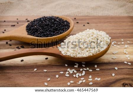 Sesame seed in wooden spoon. Black and white sesame set up on wooden board #465447569