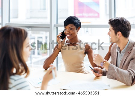 Cheerful african american young businesswoman talking on cell phone on business meeting in conference room #465503351