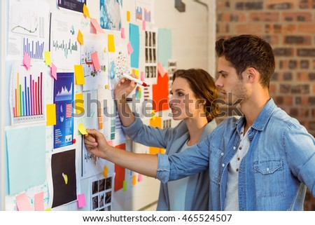 Business executives putting sticky notes on whiteboard in office #465524507