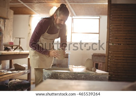 Male potter putting clay pottery wheel in pottery workshop #465539264
