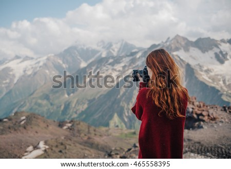 beautiful young woman with red hair photographer takes a picture of a mountain landscape on the camera while hiking