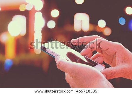 Close up of girl hands hoding modern smart phone , woman's hand using cellphone at night city, bokeh light #465718535