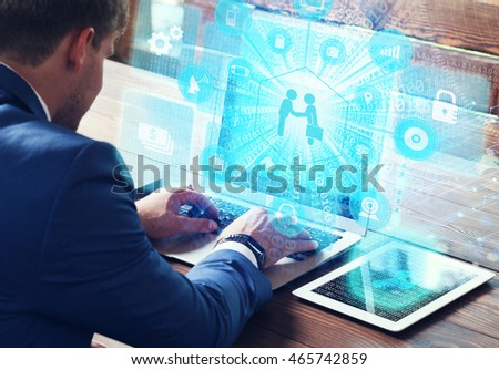 Business, technology, internet and networking concept. Young businessman working on his laptop in the office, select the icon make money on the virtual display. #465742859