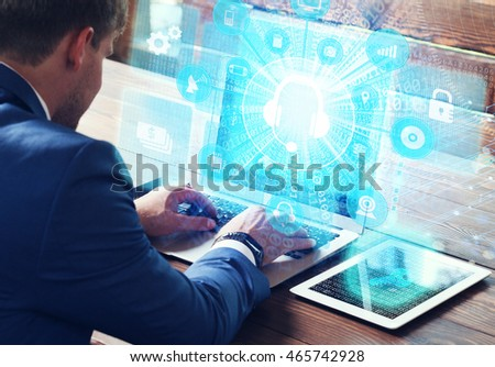 Business, technology, internet and networking concept. Young businessman working on his laptop in the office, select the icon Customer Support on the virtual display. #465742928