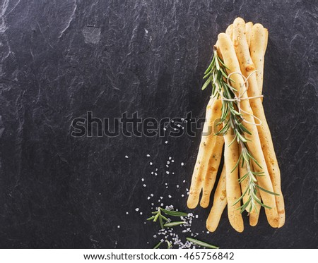 Fresh homemade crispy bread sticks with thyme and sea salt on a black background with fresh herbs. selective focus #465756842