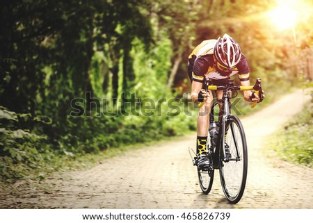 Motion photography of ride biking sport man on the road of the park of countryside forest, vintage process.