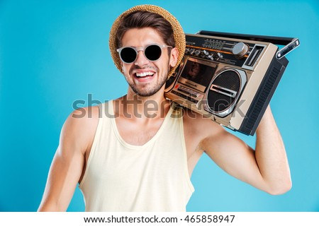 Portrait of happy young man in hat and sunglasses with boombox over blue background #465858947