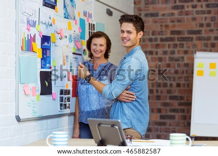 Portrait of business people standing near whiteboard in office #465882587