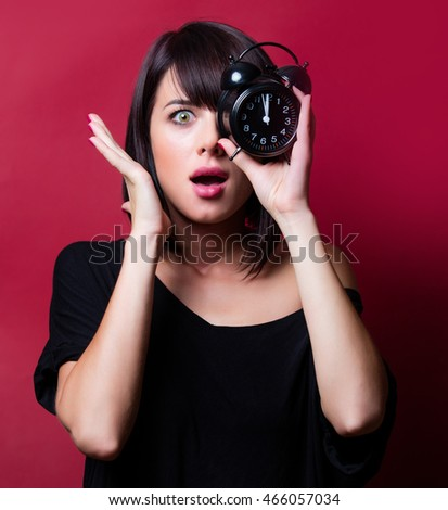 portrait of the beautiful young woman with alarm clock on the vinous background #466057034