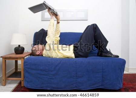 Businessman, with his jacket off, lying on a couch, and working on his laptop, looking happy