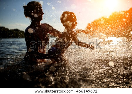 mother swim with baby in blue water at sunset; female with child bathe in lake or river and making water drops; #466149692
