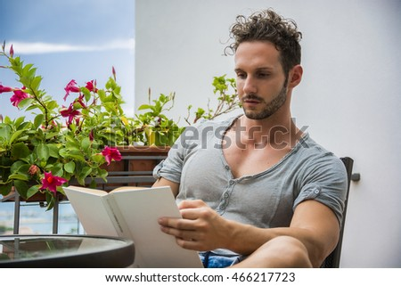 Handsome athletic young man reading book outside sitting on terrace in a summer day #466217723