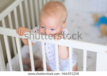 Baby boy with blue eyes standing in crib #466391258