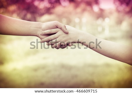 Close up on a man and a woman holding hands at green background,Hand help and hope concept,helping hand #466609715