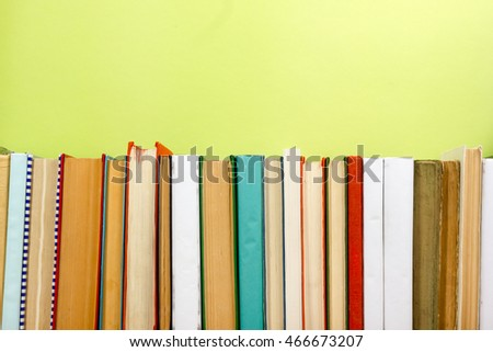 Colorful composition with vintage old hardback books stacking, diary on wooden deck table and green background. Back to school. Copy Space. Education. #466673207