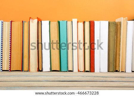 Books on grunge wooden table desk shelf in library. Back to school background with copy space for your ad text. Old hardback no labels, blank spine #466673228