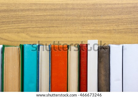 Books on grunge wooden table desk shelf in library. Back to school background with copy space for your ad text. Old hardback   no labels, blank spine #466673246