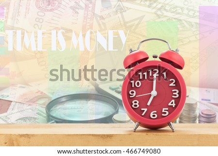 Red old fashioned alarm clock on Calculator with coin and Magnifying glass on money banknotes Euro and Dollars,with Written word Time is money #466749080