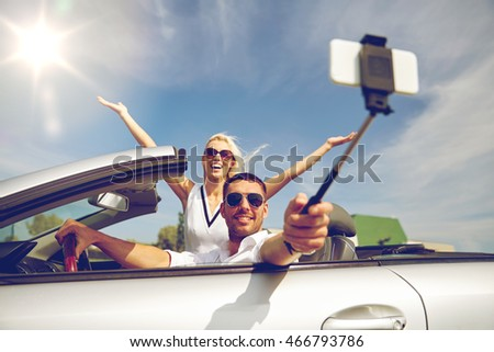 road trip, travel, couple, technology and people concept - happy man and woman driving in cabriolet car and taking picture with smartphone on selfie stick