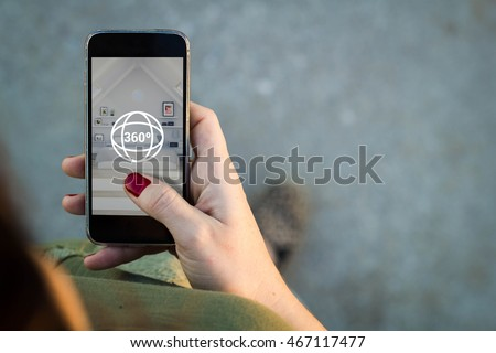 Top view of woman walking in the street surfing 360 degree view in her mobile. All screen graphics are made up. Royalty-Free Stock Photo #467117477