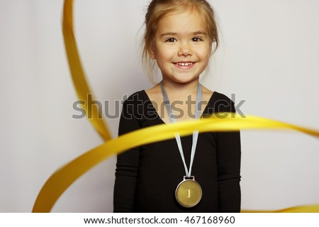 Pretty small girl in black sportswear with yellow ribbon and gold medal on her neck over white background, rhythmic gymnastics, indoor portrait, sport and health concept