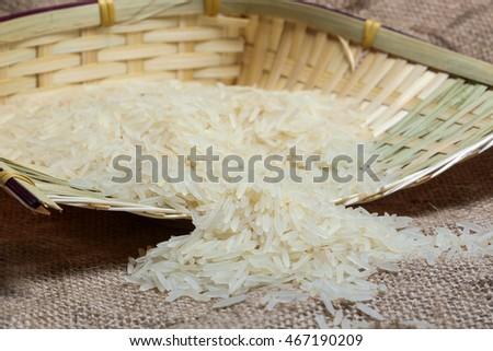 White long grain rice on jute bag and bamboo pot metal scoop #467190209