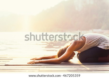 Beautiful woman practicing Yoga by the lake - Sun salutation series - Balasana or child's position - Toned image