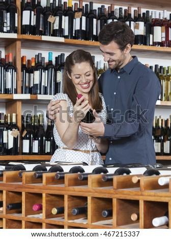 Happy Couple Holding Wine Bottle In Shop #467215337