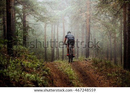 male athlete mountainbiker rides a bicycle along a forest trail. in forest mist, mysterious view Royalty-Free Stock Photo #467248559