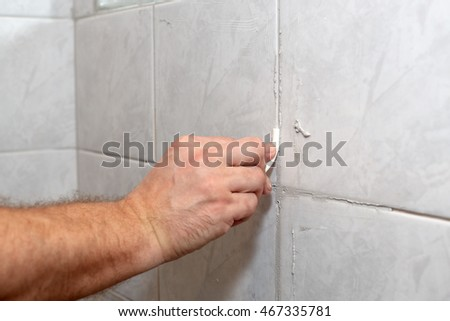 The male hand with the rubber stick applies grout on a seam between tiles in a bathroom. Home repairs. #467335781