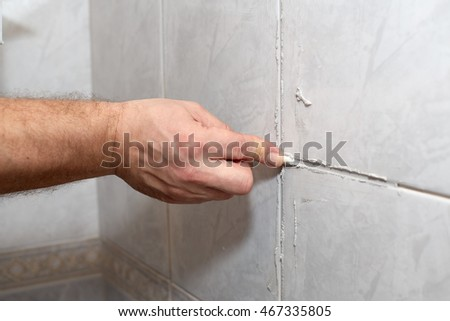 The male hand with the rubber stick applies grout on a seam between tiles in a bathroom. Home repairs. #467335805