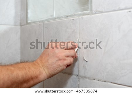 The male hand with the rubber stick applies grout on a seam between tiles in a bathroom. Home repairs. #467335874