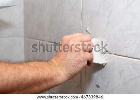 The male hand with the rubber spatula applies grout on a seam between tiles in a bathroom. Home repairs. #467339846